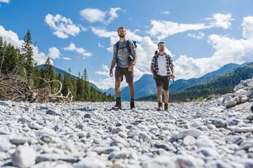 Germany, Bavaria, two hikers walking in dry creek bed