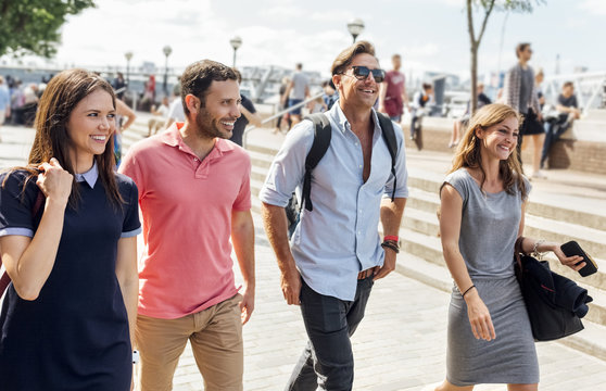 UK, London, group of friends walking along the banks of the Thames River