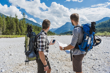 Germany, Bavaria, two hikers  standing in dry creek bed orientating with cell phone and map