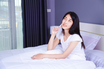 beautiful woman thinking on bed in bedroom