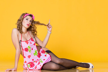 Young dreaming woman dressed in pinup style sitting on floor looking up and holding her hair in arm