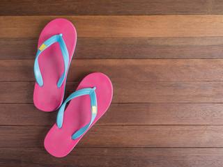 Pink flip flop on wooden floor 2