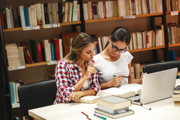 Two female students study in the school library.Learning and preparing for university exam.