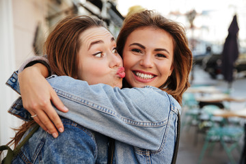 Close-up photo of two  happy pretty woman friends in jeans jacket hugging each other on city street