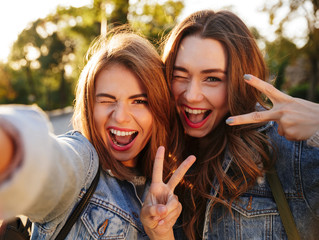 Two happy young brunette woman having fun while taking selfie on mobile phone, outdoor