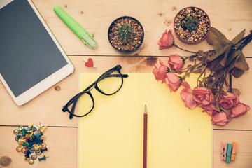 Top view of Creative writing concept with notebook,pencil,glasses and pink rose on wood background. Copy space for text. Vintage or retro tone. Blank area for text or message