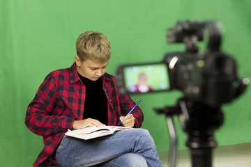 Young boy blogger records video on a green background. A boy blogger records a video on a green background at home on a video camera. A blogger is sitting on a chair with a laptop