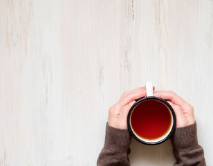 Female hands holding a mug of hot black tea. Cold winter, warm clothes, sweater. Top view. White aged wooden background