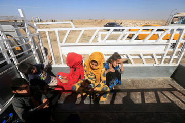 Displaced people riding in trucks and cars head back to their homes in Hawija, on the outskirts of Kirkuk