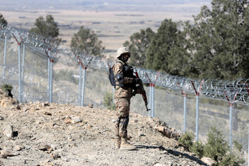 A soldier stands guard along the border fence at the Angoor Adda outpost on the border with Afghanistan in South Waziristan