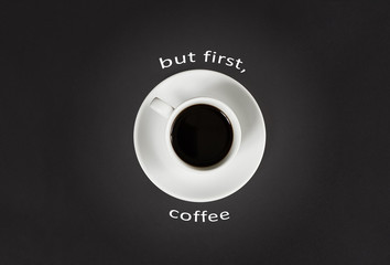 Coffee in white cup with a lettering But first coffee on black slate background