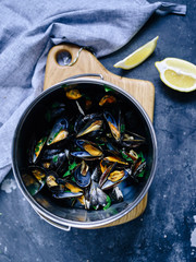 A pot full of cooked blue mussels with parsley and lemon