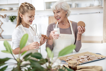 Excited child tasting self-made cookies with granny
