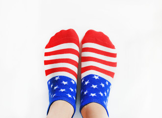 Person Wearing Socks with American Flag. Pair of cotton socks in red, blue and white color, United States flag pattern. Women and men fashion accessory isolated on white empty background copy space