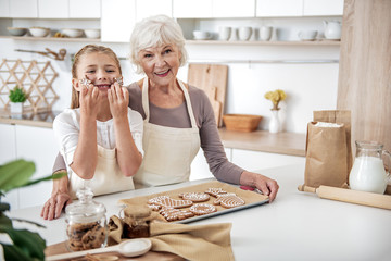 Joyful grandmother and child baking pastry together