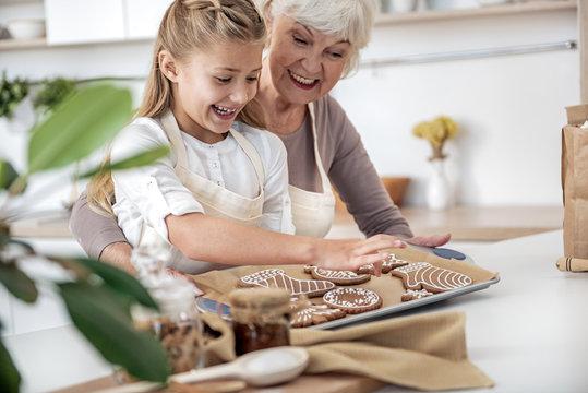 Joyful old woman giving sweet pastry to kid