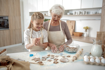 Happy girl baking sweets with her granny