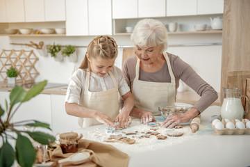 Happy grandmother teaching kid to bake