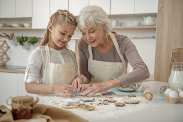 Cheerful grandchild learning to make pastry in kitchen