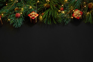 Christmas. Xmas toys and spruce branch on black background top view. Space for text