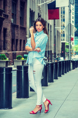 Beautiful Street Fashion Girl. Young Argentine Woman traveling in New York, wearing light blue striped shirt, white destroyed jeans, red sandal heels, standing on vintage street, looking at you. .
