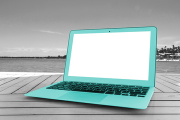 Turquoise Laptop computer on wooden table. Front ocean view. Tropical island background. Open blank laptop computer empty space. Front view with copy space. Black and white