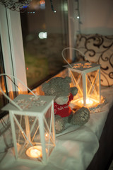 white Teddy bear in a red shirt sitting on the windowsill between 2 Vintage white lanterns with small candles lit in them lighting up the room On Christmas eve .