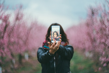 woman taking photos to the pink trees