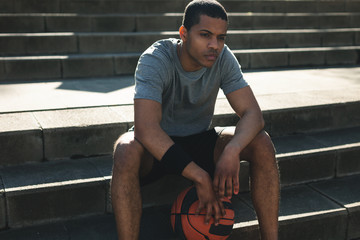 Young african american male basketball player resting after training session.