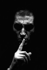 Angry mature man with an aggressive look making the silence sign in a threatening and creepy way. Black and White, black background. Concept for secret, threat, anger, rage, violence, danger, menace.
