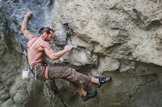 Muscular man rock climbing a difficult route