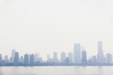 Silhouette of buildings next to the sea. Polluted skyline in Mumbai, India