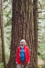 Attractive mature woman on a hike through old growth forest