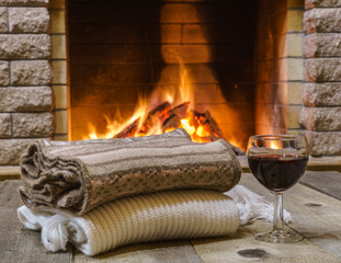 Glass  of  red wine  and  woolen things near  cozy fireplace, in country house, winter vacation, horizontal.