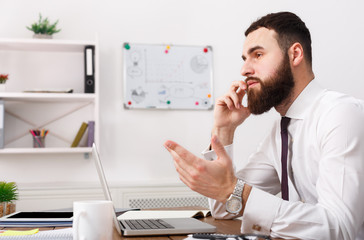 Serious businessman talking on cell phone with laptop in modern office
