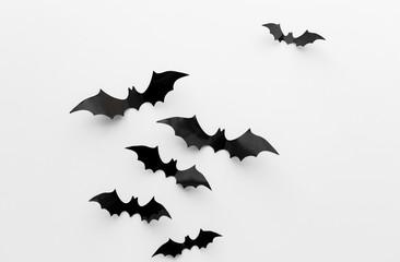 black paper bats over white background