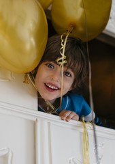 Little boy looking at camera holding balloons while laying in the wardrobe