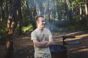Man smiling by campfire