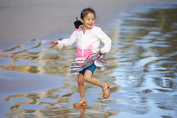 happy asian girl playing on the beach