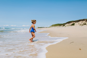 a girl in a blue swimsuit walks along a beach in the summer