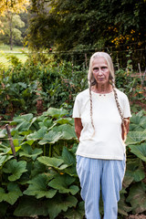 Elderly woman with blonde braids standing in front of vegetable garden