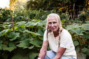 Elderly blonde woman with braids sitting in a vegetable garden row