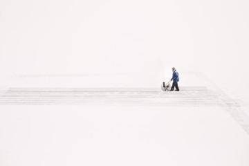 Man pushing snow blower on lake to prepare an ice rink