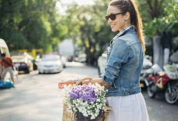 Woman carrying wooden basket full of  spring flowers