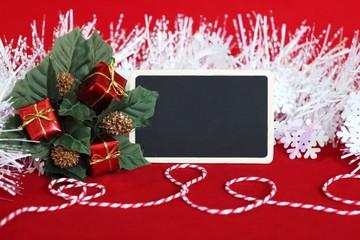 Un tableau vide en forme de rectangle pour écrire un message ,des feuilles garnie de cadeaux rouge , une guirlande blanche givrée et un fil rouge et blanc pour la décoration de fêtes.