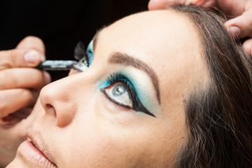 Makeup artist applying blue eyeshadow on white woman eyes