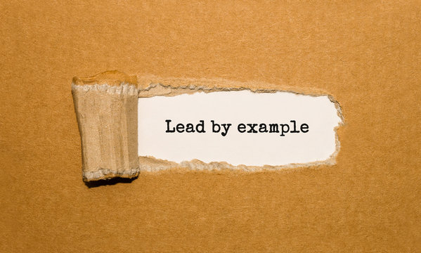 The text Lead by example appearing behind torn brown paper