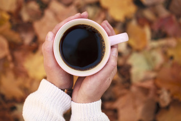 Сup of black coffee on a background of autumn foliage