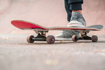 Red skate Legs in sneakers. Sports, teenager, riding area.