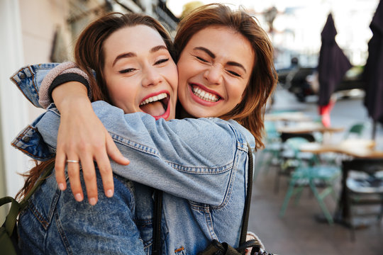 Close-up photo of laughing woman friends hugging each other on city street